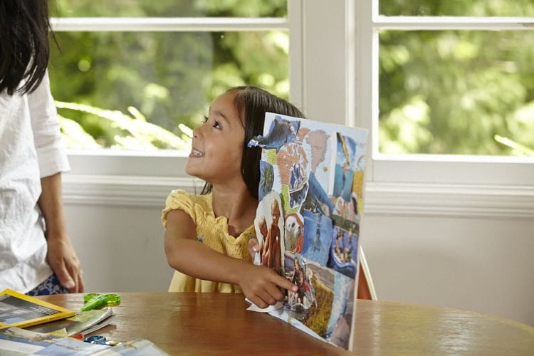 little girl proudly showing her collage to mom