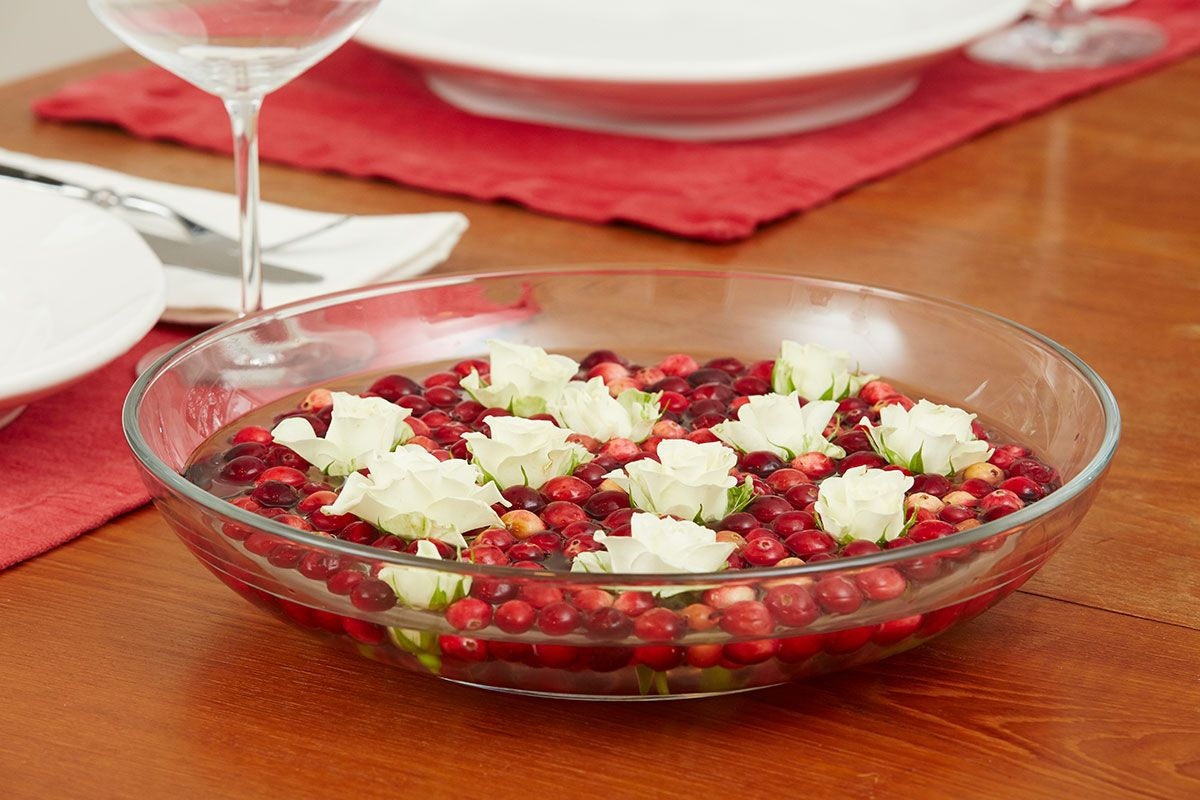 cranberries and white flowers floating in water in bowl