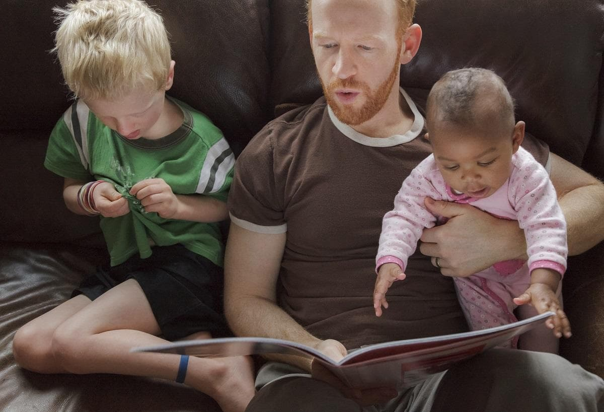 dad reading to two kids one adopted