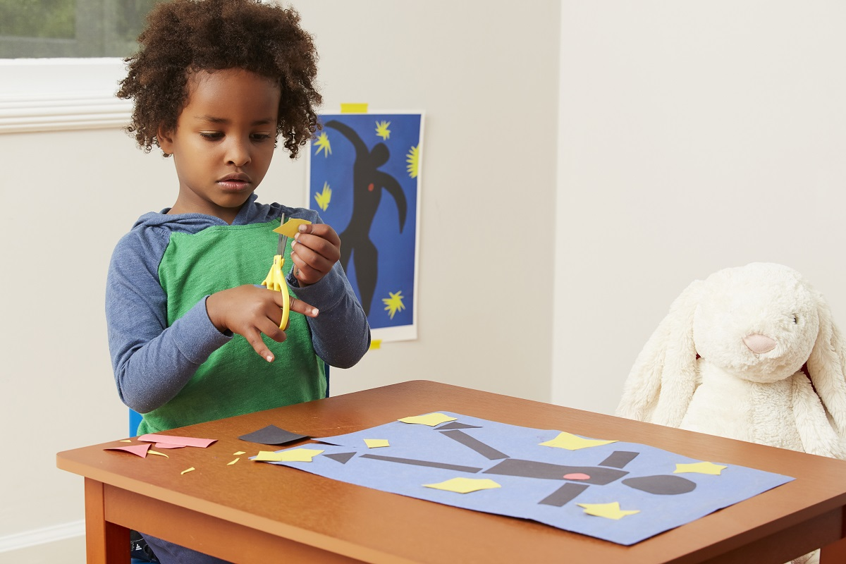 Toddler boy cutting shape with scissors