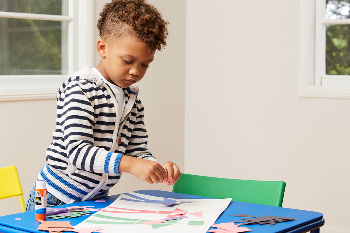 Wide shot of boy pasting geometric paper shapes onto paper