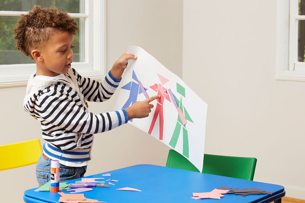 Young boy holding up his Picasso-inspired art.
