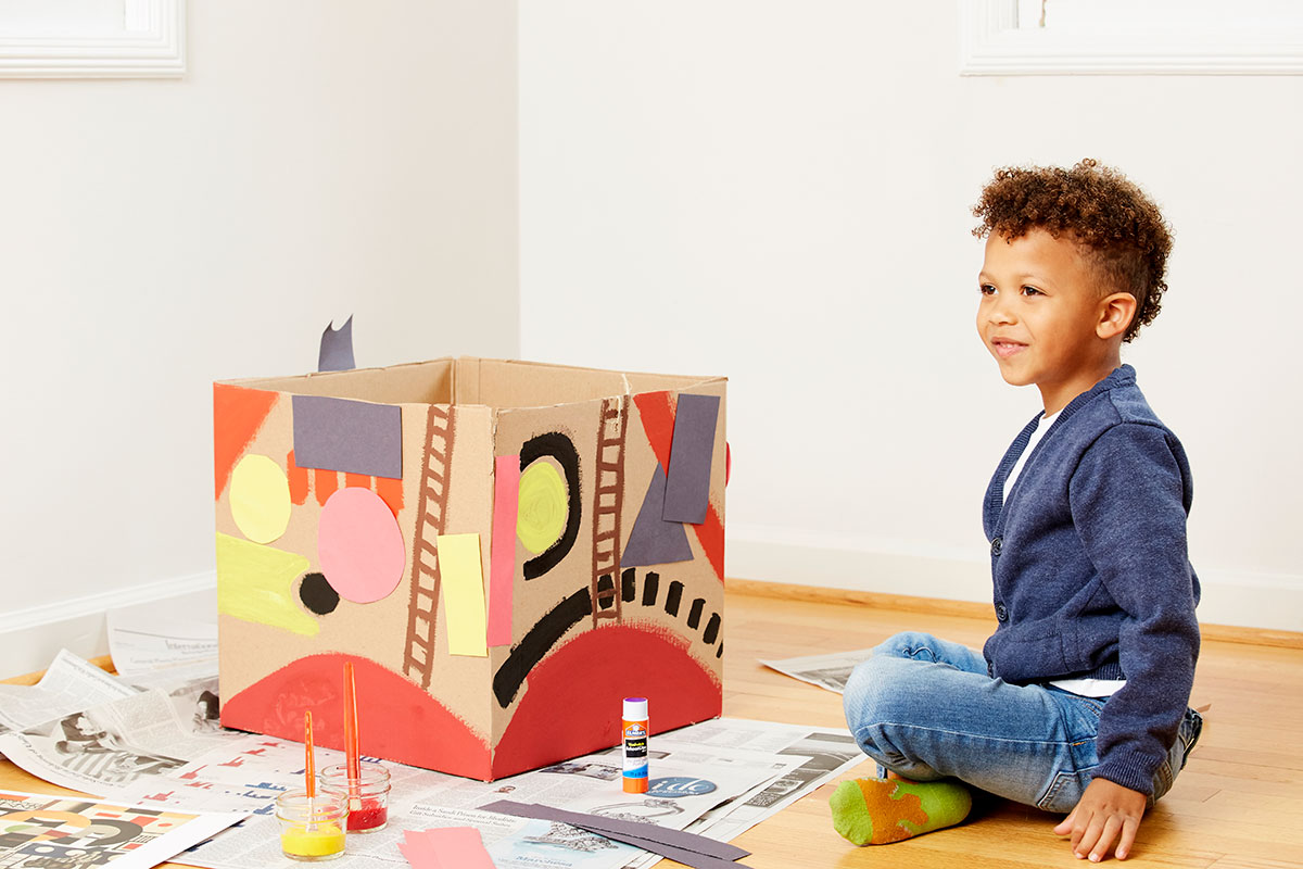 Child sitting on floor next to cardboard tugboat