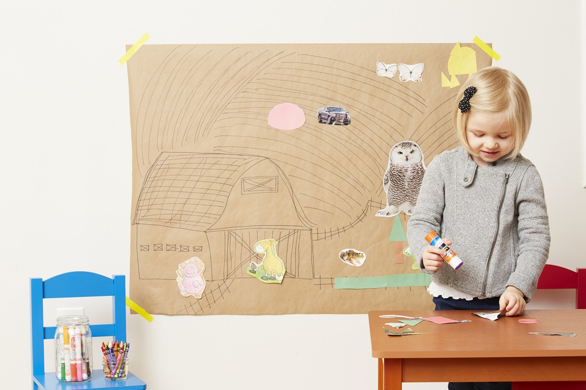 Toddler glues pictures on wall mural