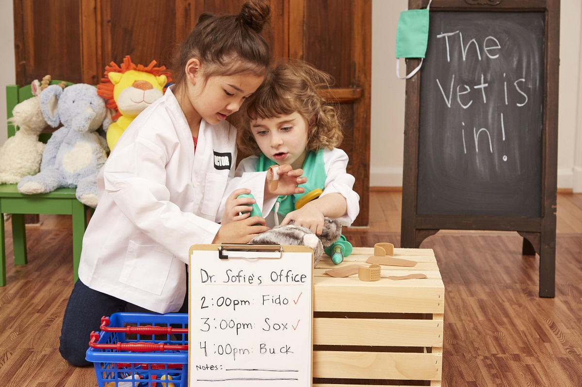 Two girls pretend playing veterinarian examining a cat stuffed animal