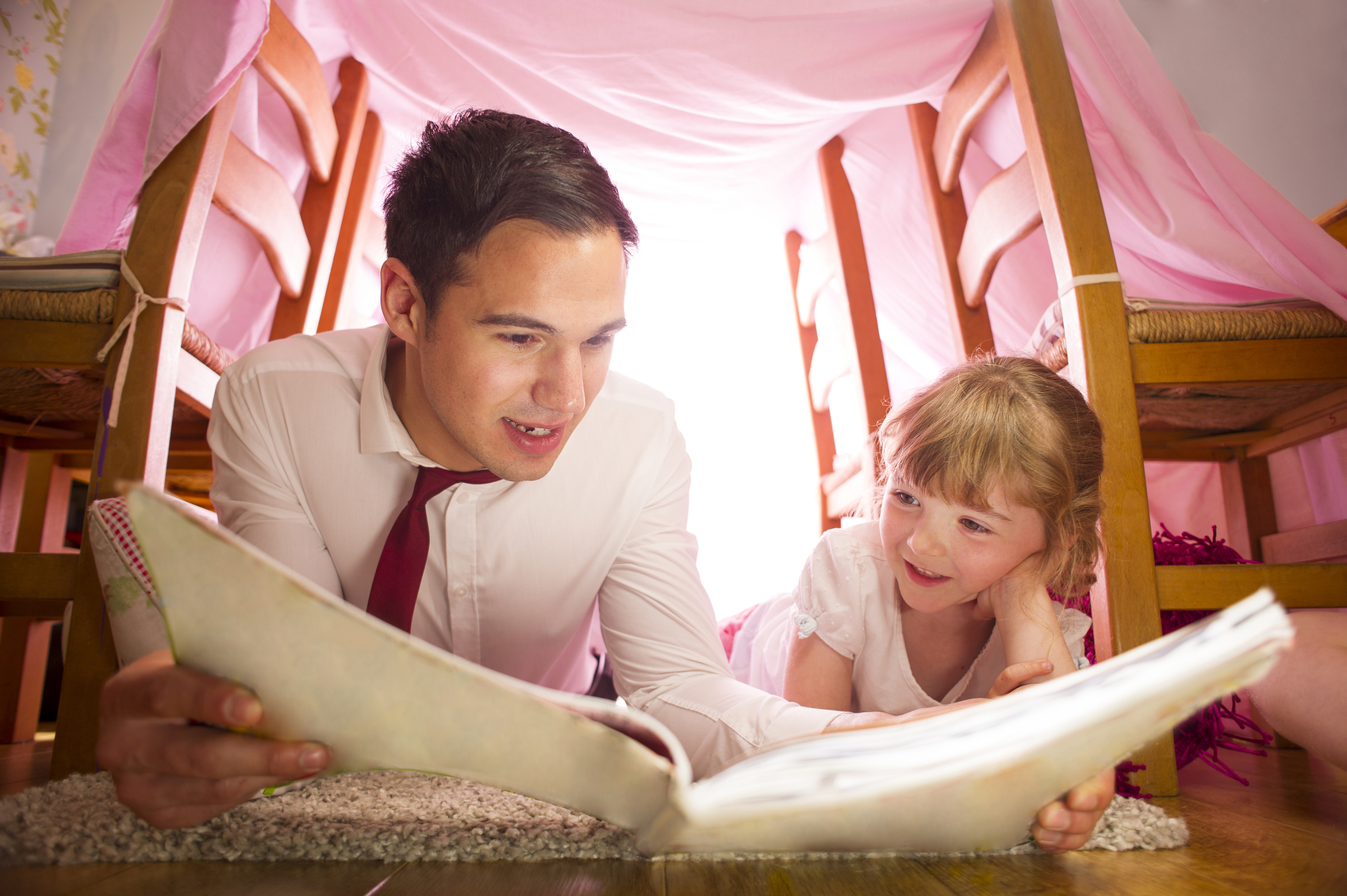 Father and daughter reading in a blanket fort