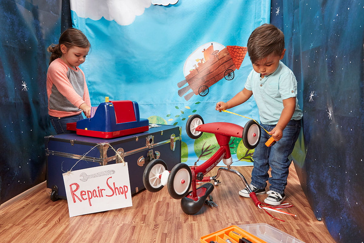 Girl and boy pretending to play tricycle repair shop