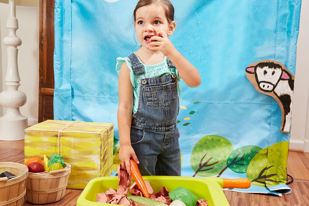 child in overalls play food wheelbarrow