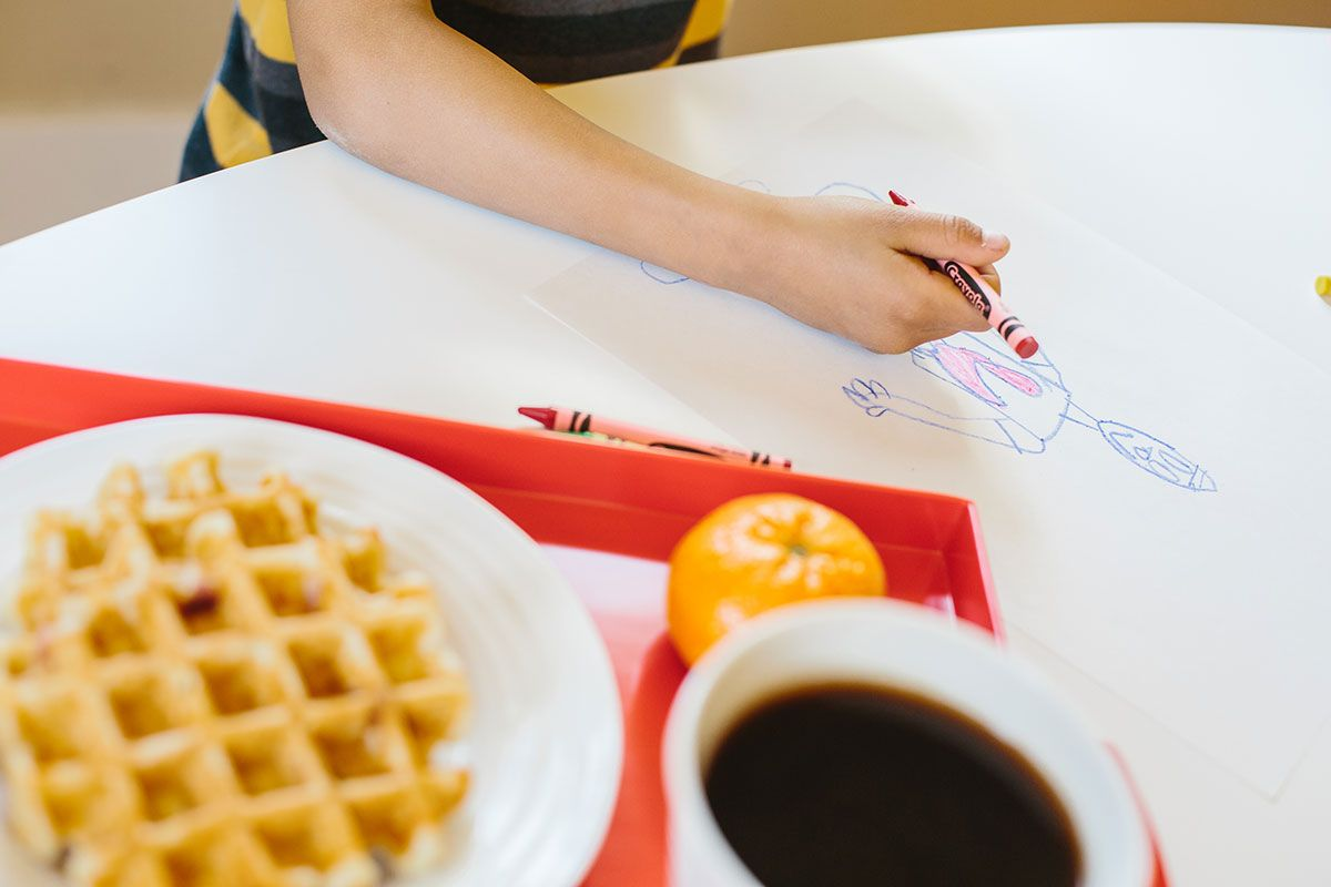 child coloring near waffles