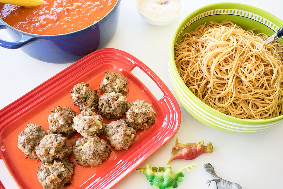 overhead shot of meatballs, pasta, and sauce in bowls