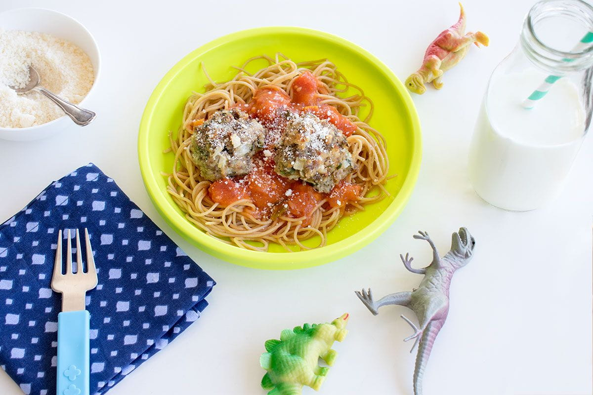 prepared meatballs in a bowl cup of milk fork napkin dinosaur toys