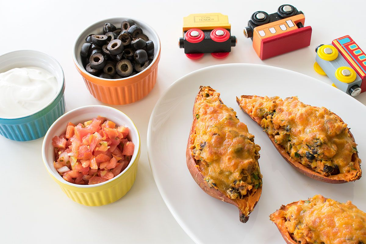 stuffed potatoes with tomatoes, black olives, and cream in bowls