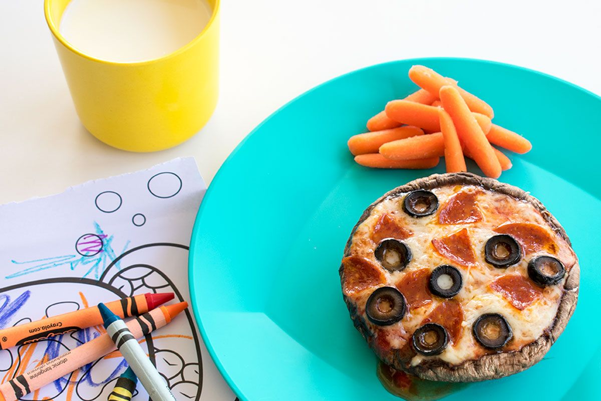 mini mushroom pizza round with carrot sticks, crayons, and milk