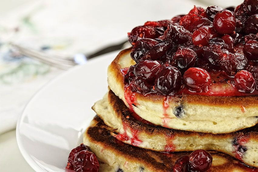 cranberry sauce on top of pancake stack Photo by Stephanie Frey / iStock