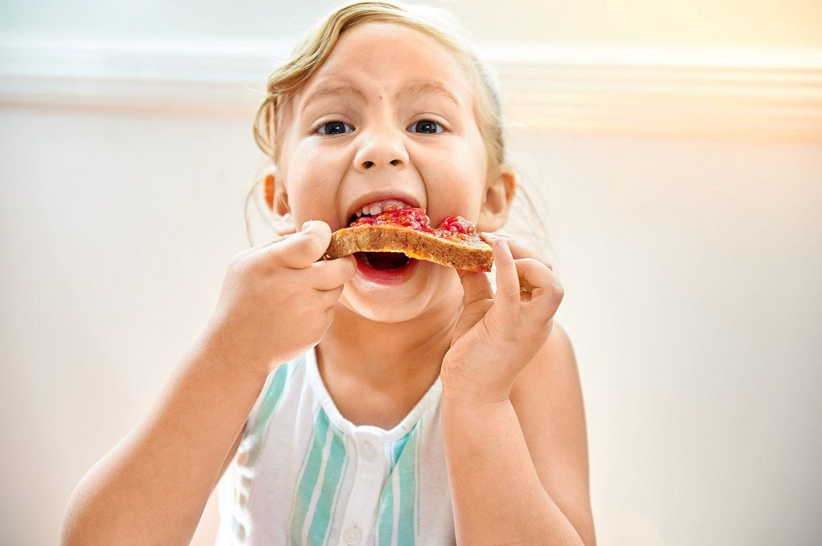 girl with big bite of jam on toast