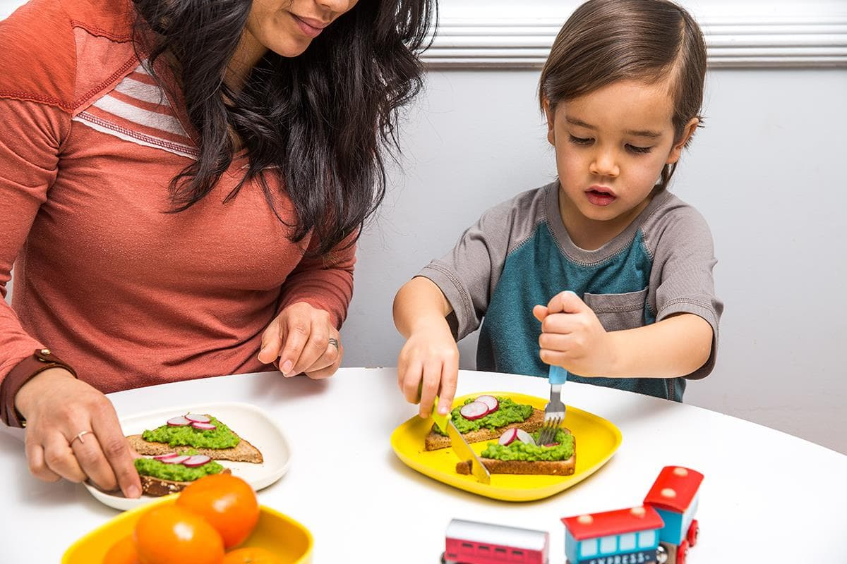 child and mom with cheesy pea toast at table