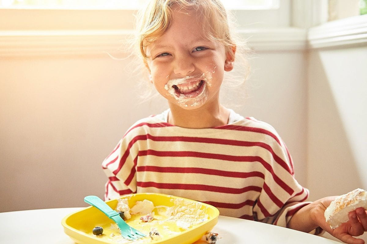 smiling girl with empty plate whipped cream on face