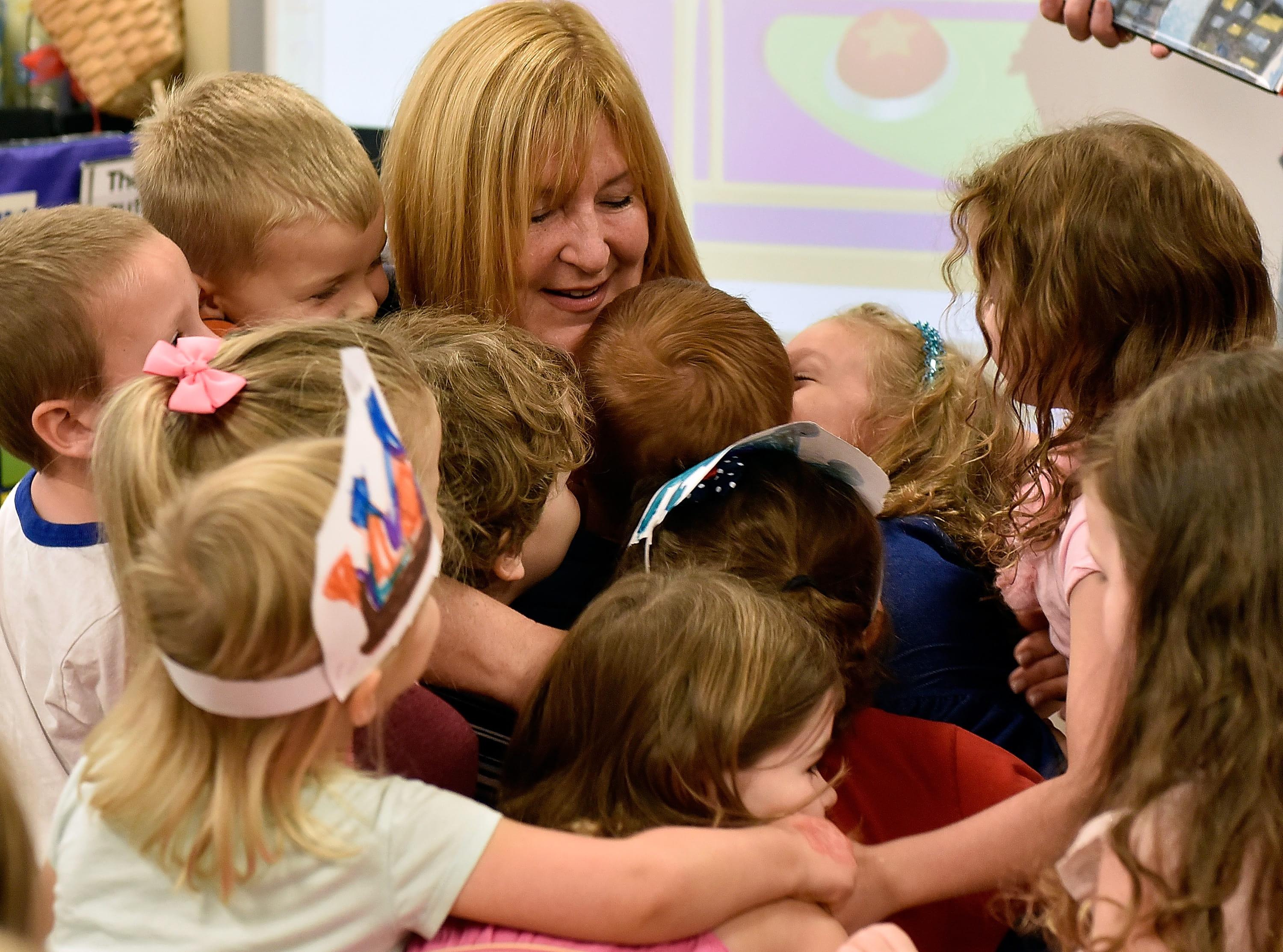 After winning an Early Childhood Educator Award, preK teacher Sue Davies was engulfed by warm hugs. Photo by Getty Images