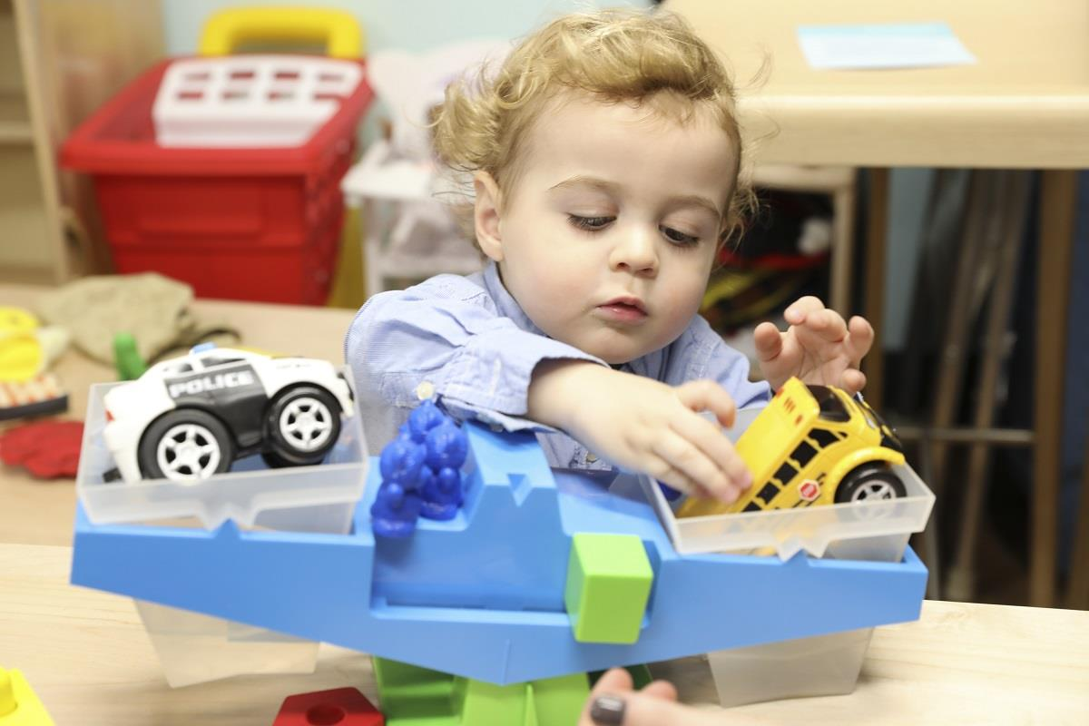 toddler playing with toy trucks