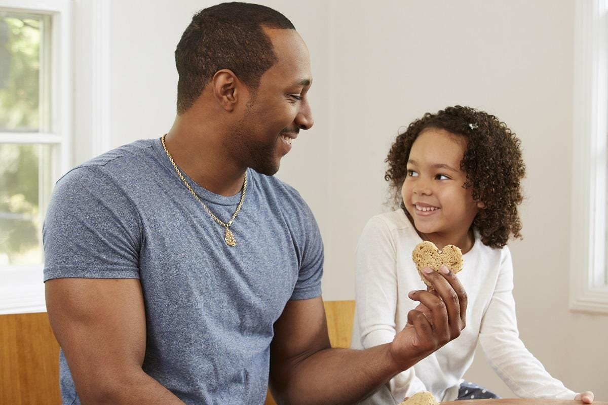 Father giving daughter heart-shaped cookie