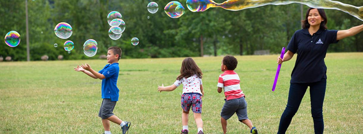Children playing with bubbles in a field.
