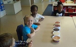 Preschool students making people out of multicultural play-dough.