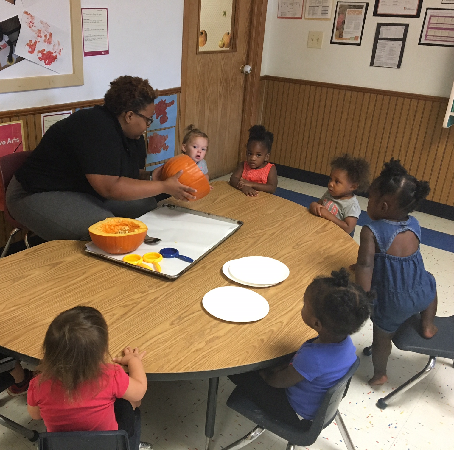 Ms. Andi is letting the children use their cognitive development by doing a wet and messy project, exploring pumpkins. They are coming to understand and interacting with the world around them.