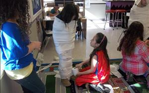 Our School Age classroom is learning about Ancient Egypt and this is them preforming a mummy wrap.