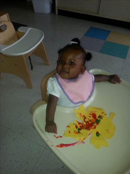 Infant Student exploring finger painting.