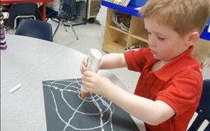 One of our Prekindergarteners creates a spiderweb.