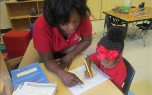 Ms. Carrie is helping a child write the letters in the Preschool class