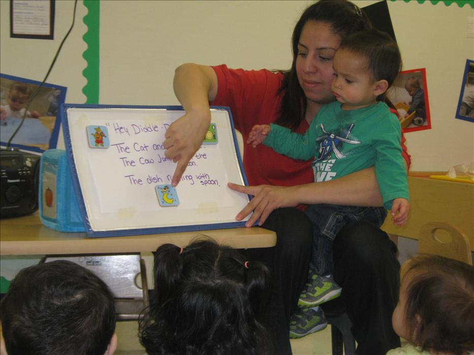 Ms. Marisol is teaching her two year olds a new song.  In addition to sing it she writes it and draws pictures. Creating a print rich environment is the first step in learning to read and write.