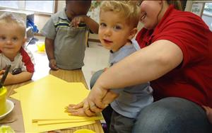 Ms. Holly and toddlers working on some fun art by creating little ducklings using only handprints.