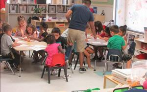 Mr. Chris having a lesson with his PreK class about color mixing!