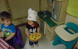 Emma pretending to be a pizza chef in dramatic play.