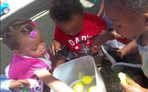 Enjoying sensory exploration while 'washing' fruit and splashing in water.
