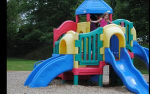 One School Age student searches the playground structure while her friends play a game of hide-and-seek.