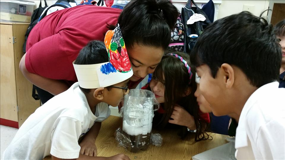 "Ms.Carla assisting School Age students on their sense of ""smell"" with this fun science experiment."