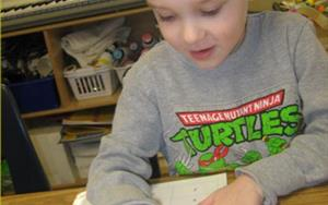 One of our learning adventure phonics students practices his reading skills.