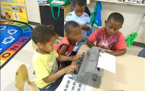 Children practicing typing braille. Writing their names and trying to make sentences