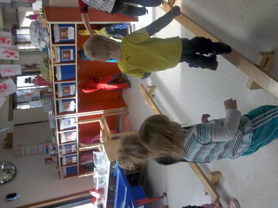 Preschool class work on balance by walking on the balance beams