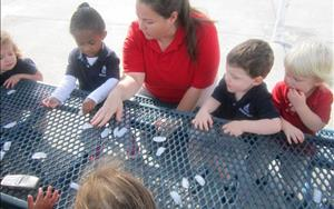 Ms. Kathy and friends are exploring ice melting in our Discovery Preschool class
