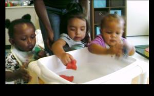 Babies playing in the water table  during water play.