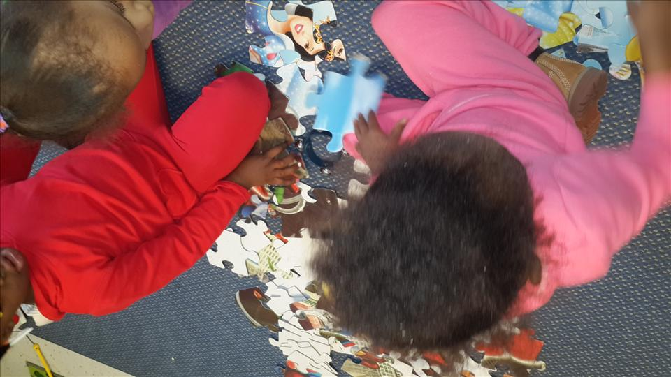 Preschool students working on a puzzle together.