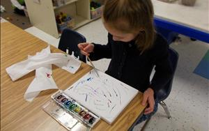One of our Prekindergarteners creates a canvas for our classroom.
