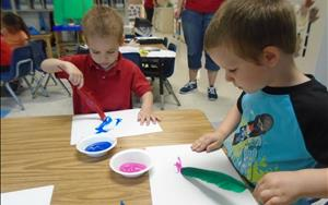 Preschoolers Painitng with Feathers