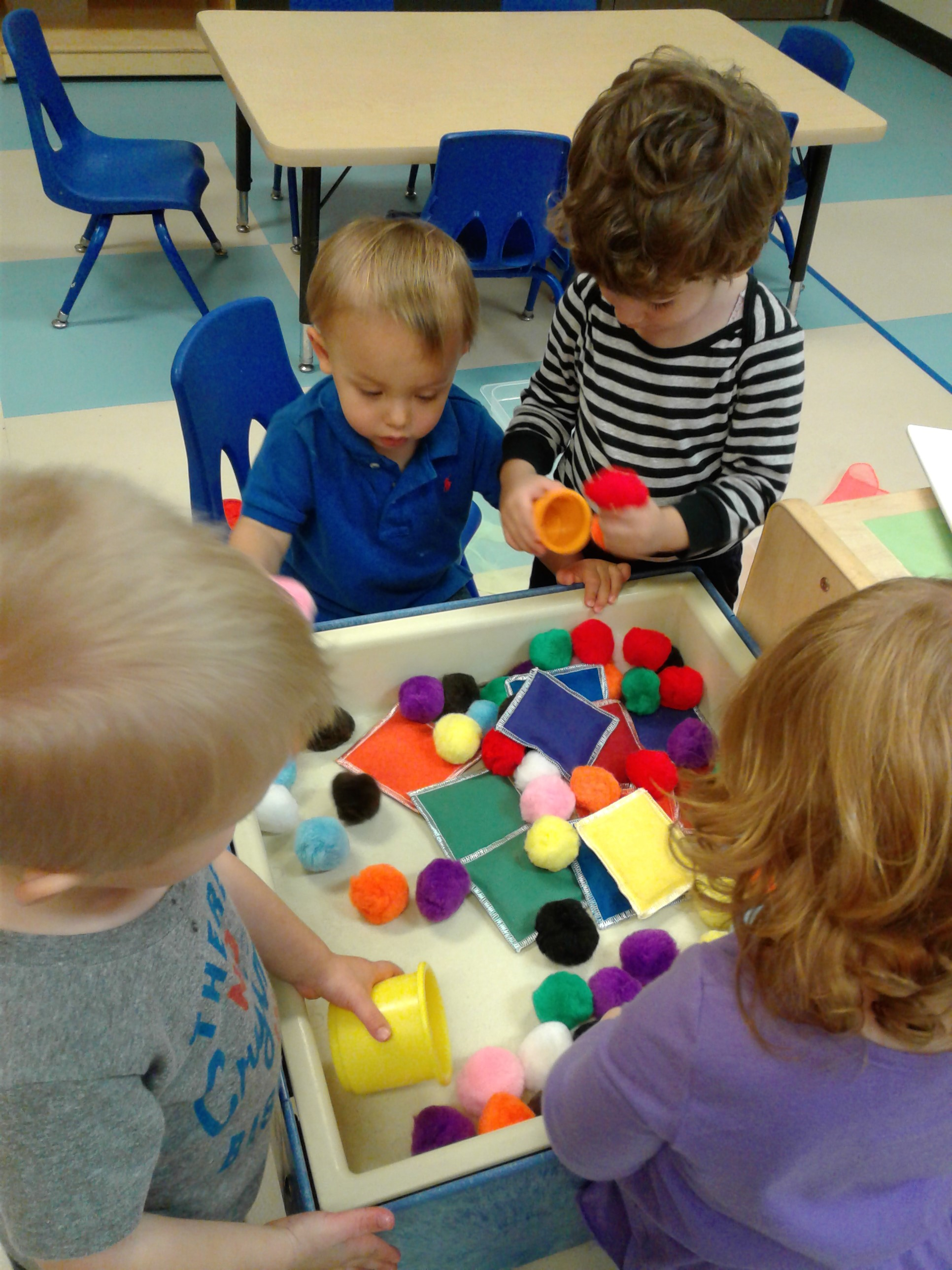 Sensory play is so important for children. All of our classrooms have sensory tables with new and exciting materials for children to play with and explore. These toddlers are using their fine-motor skills to scoop pom-pom balls into cups.