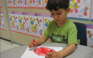 One of our children drawing a watermelon and writing the word watermelon during our Letters and Sounds Learning Adventures class.