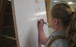 One of our children writing during our Vowels and Blending Learning Adventures class.