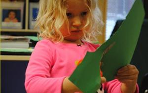 A preschooler focuses intently on cutting her paper for her creative art project.